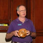 Ron Lindsay holding a natural edged avocado bowl with a hollow form hidden inside.