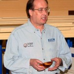 Russ holding a bowl with sheet of brass laminated between two halves of exotic wood blank.