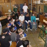 Using a straw broom to illustrate grain direction and cutting procedure for 8th graders who make bowls.