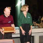 Out going president Al Geller holding huge block of cocobolo presented to him by incoming president Martha