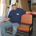 Rob sitting on his bench made from turned spindles and woven maple stripps