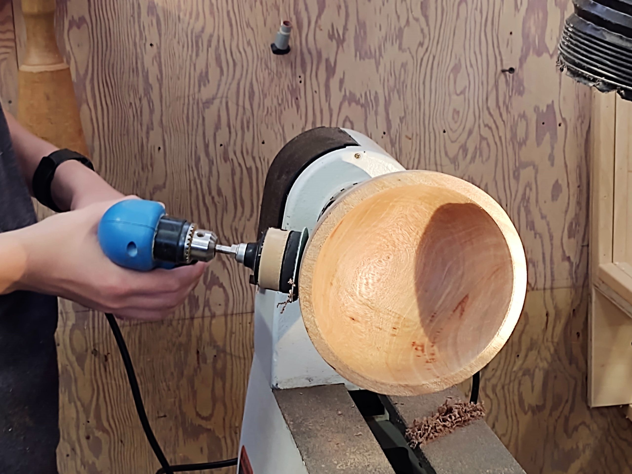 A student power sanding their bowl on the lathe in woodshop.